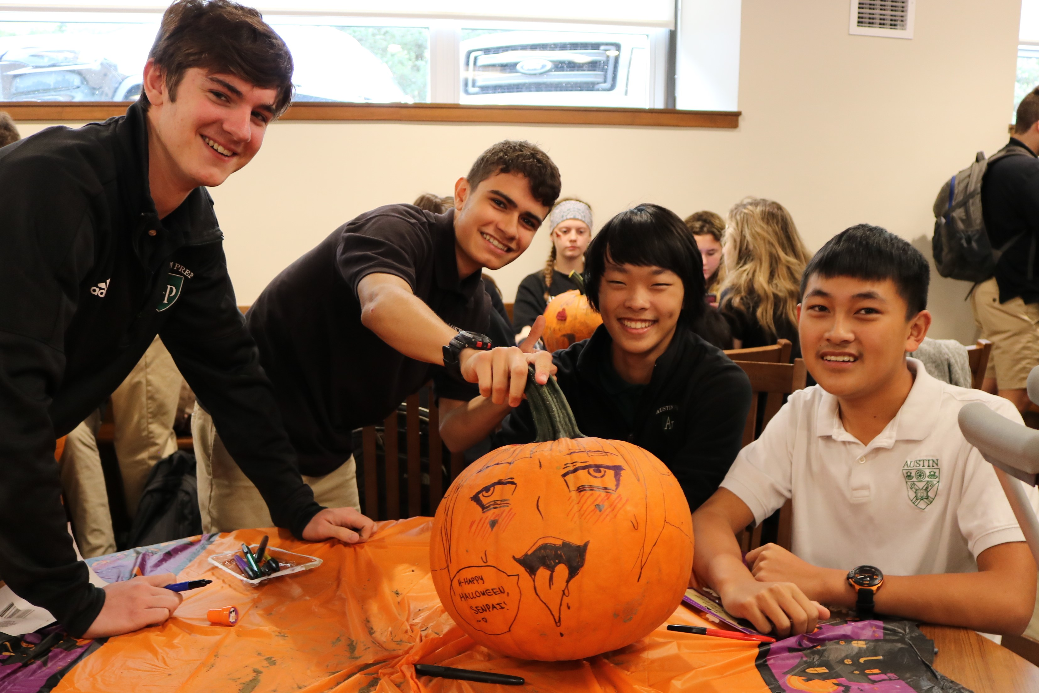 Students drawing on a pumpkin